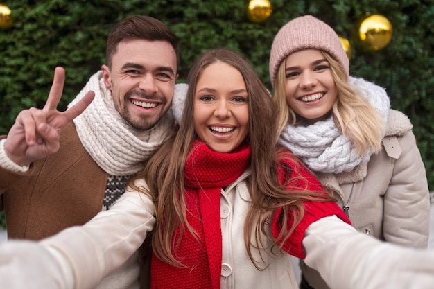Happy young woman in outerwear taking selfie with friends against decorated coniferous tree on christmas day
