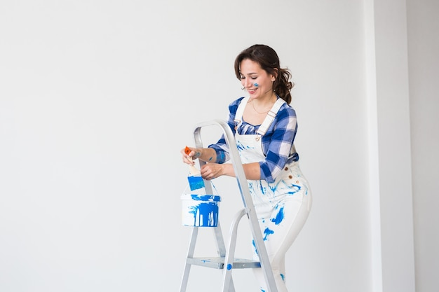 Happy young woman paint wall at home with copy space