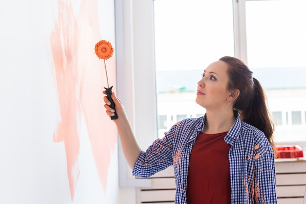 새 집에 페인트 롤러와 함께 행복 한 젊은 여자 그림 인테리어 벽. 벽에 페인트를 적용하는 롤러를 가진 여자.