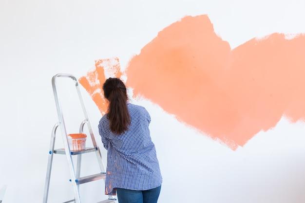 새 집에 페인트 롤러와 함께 행복 한 젊은 여자 그림 인테리어 벽. 롤러를 가진 여자