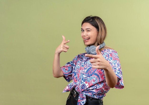 Una giovane donna felice in camicia stampata paisley che indossa le cuffie che puntano con il dito indice mentre lo guarda su una parete verde
