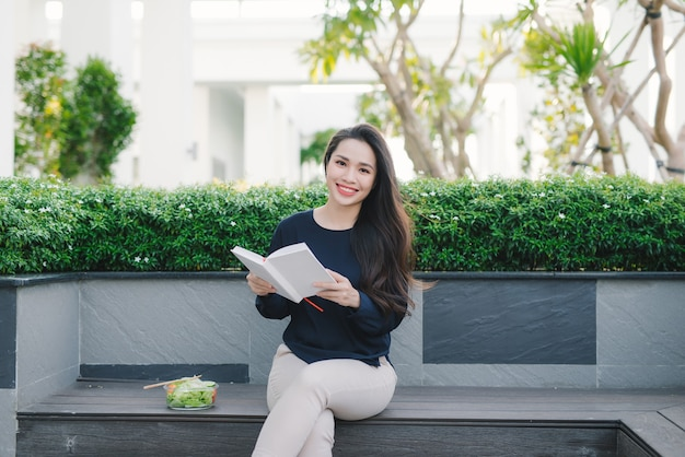 Happy young woman in park on sunny summer day reading book. cheerful beautiful girl on beautiful day.