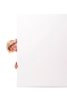 Happy young woman peeking from behind whiteboard