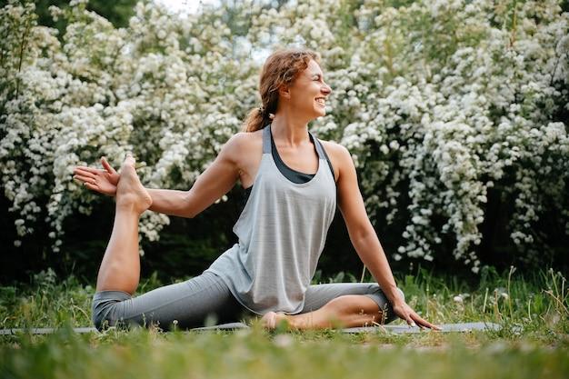 행복한 젊은 여성은 공원에서 여름에 야외에서 다리 스트레칭 운동을 한다