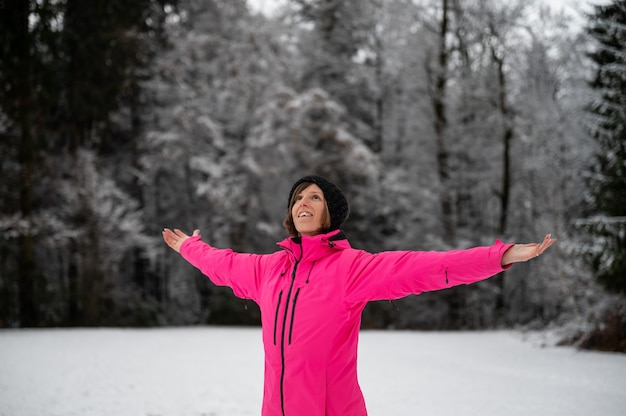 Happy young woman in pink winter jacket standing in beautiful snowy nature with her arms spread widely.