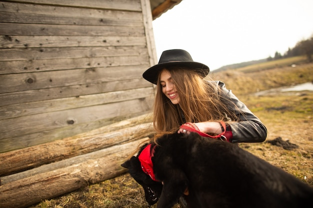 Happy young woman plaing with her black dog