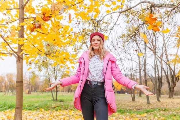 자연의 아름다운 가을 공원에서 떨어지는 노란 잎 아래에서 노는 행복한 젊은 여성은 야외에서 산책합니다. 십 대 소녀가을 오렌지 단풍을 던졌습니다.