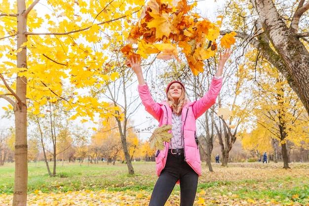 Счастливая молодая женщина играет под падающими желтыми листьями в красивом осеннем парке на прогулках на природе