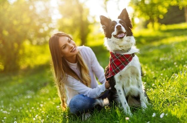 Счастливая молодая женщина, играя со своей собакой в парке на открытом воздухе