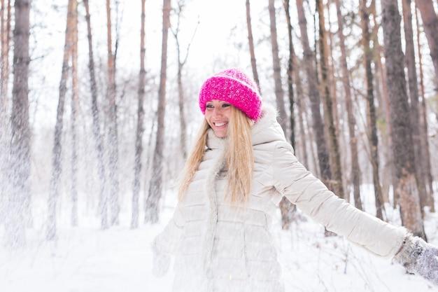 幸せな若い女性は屋外の雪に覆われた森で雪と遊ぶ