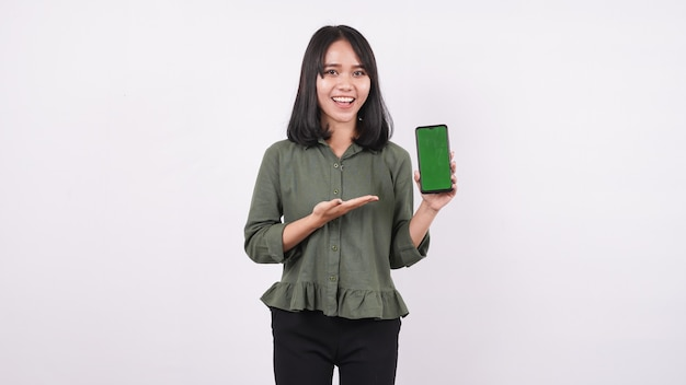 흰색 격리 된 벽에 녹색 전화를 가리키는 행복 한 젊은 여자