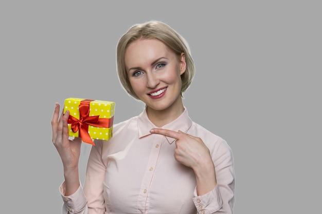 포장 된 선물에서 가리키는 행복 한 젊은 여자. 회색 배경에 작은 선물 상자를 보여주는 행복 한 미소 비즈니스 여자.