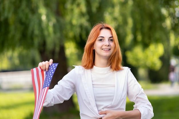 미국 국기와 함께 포즈를 취한 행복한 젊은 여성이 여름 공원에서 야외에 서 있는 뻗은 손에 그것을 들고 있습니다. 미국 독립 기념일을 축하하는 예쁜 소녀.