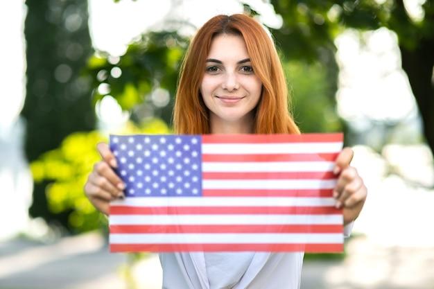 彼女の広げられた手でそれを保持しているアメリカの国旗でポーズをとって幸せな若い女性