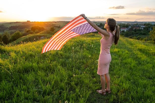 Счастливая молодая женщина позирует с национальным флагом сша, стоя на открытом воздухе на закате. положительная женщина празднует день независимости соединенных штатов. международный день демократии концепции.