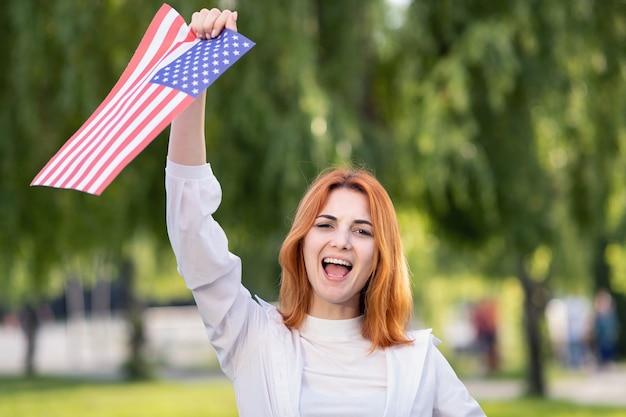 Счастливая молодая женщина позирует с национальным флагом сша, стоя на открытом воздухе в летнем парке.
