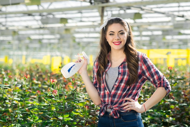 Happy young woman pouring flowers in greenhouse