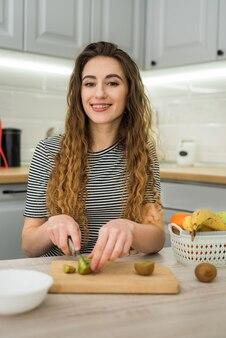 幸せな若い女性は、キッチンでの食事、健康的な食事のためにフルーツサラダをする準備をします。ダイエットの概念。