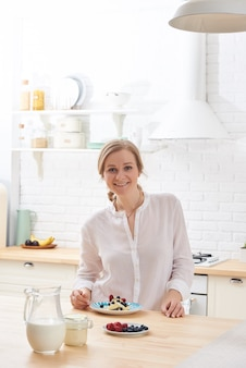 Happy young woman preparing tasty snacks at the kitchen table in the morning light