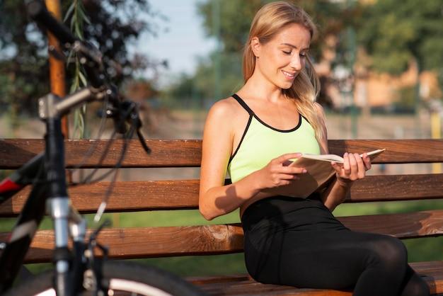 Счастливая молодая женщина, читающая книгу