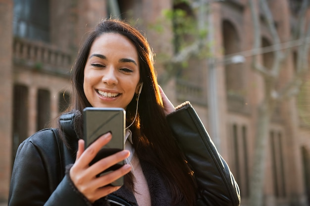그녀의 전화에서 메시지를 읽고 행복 한 젊은 여자