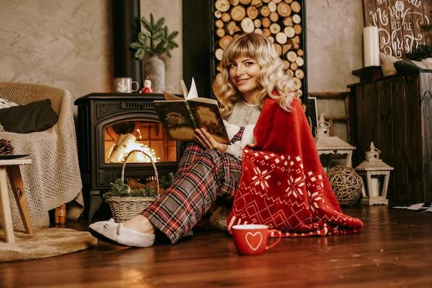Счастливая книга чтения молодой женщины перед интерьером рождества с камином. девушка одета в домашнюю уютную одежду с красным теплым пледом.