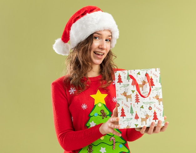 Felice giovane donna in maglione rosso natalizio e cappello da babbo natale che tiene in mano un sacchetto di carta con un regalo di natale che sorride allegramente in piedi sul muro verde