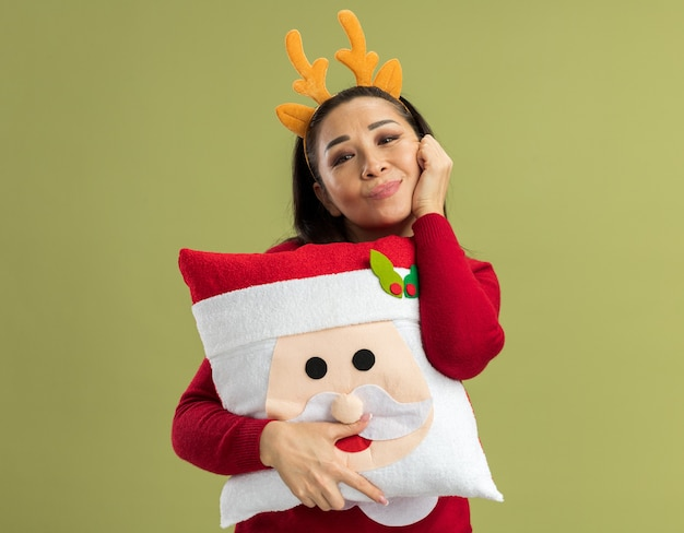 Happy young woman in red christmas sweater wearing funny rim with deer horns holding christmas pillow looking smiling cheerfully