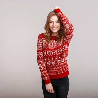 Happy young woman in a red sweater on a gray background in the studio