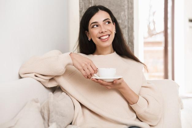 リビングルームのソファでリラックスして幸せな若い女性