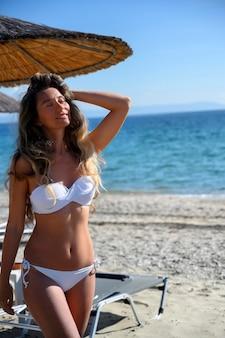 Felice giovane donna in appoggio sulla spiaggia di asprovalta, grecia