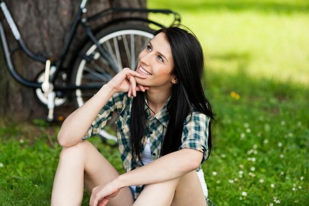 公園で休んで幸せな若い女性