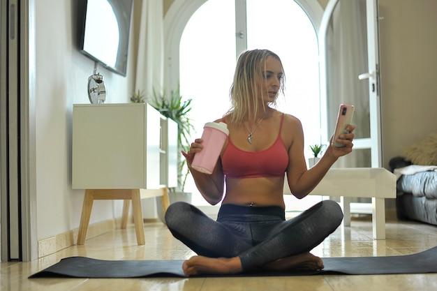 Счастливая молодая женщина, отдыхая на питьевой воде циновки для йоги и проверяя телефон