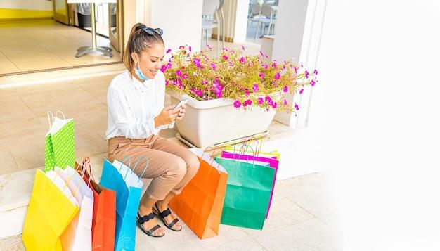 いくつかの色の紙袋の間に座って市内中心部で買い物をした後、開いた保護フェイスマスクで休んでいる幸せな若い女性。スマートフォンを使用してオンラインで購入および取引するミレニアル世代の現代人
