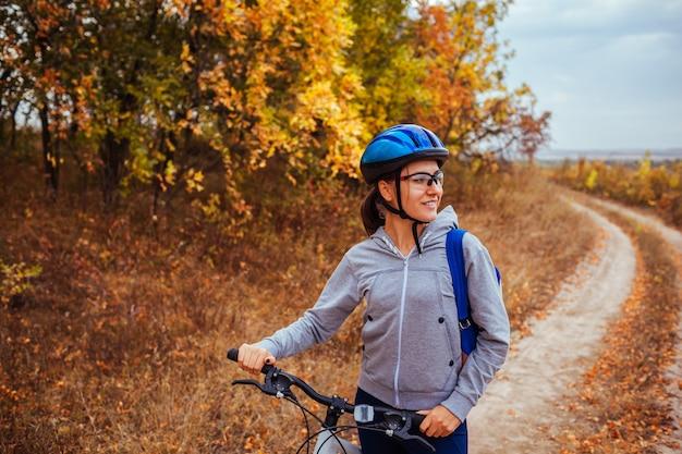秋のフィールドで自転車に乗って幸せな若い女