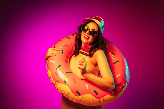 Happy young woman in a rubber beach ring, red cap and sunglasses with a candy on trendy pink neon