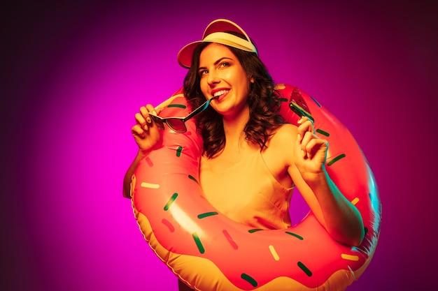 Felice giovane donna in un anello di gomma da spiaggia, berretto rosso e occhiali da sole con una caramella su neon rosa alla moda