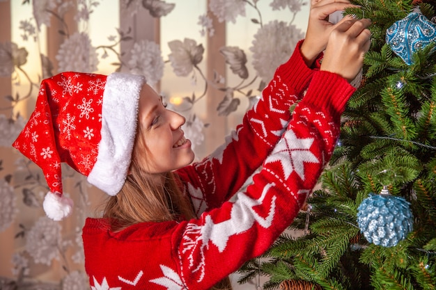 Happy young woman in santa claus hat decorating christmas tree with baubles