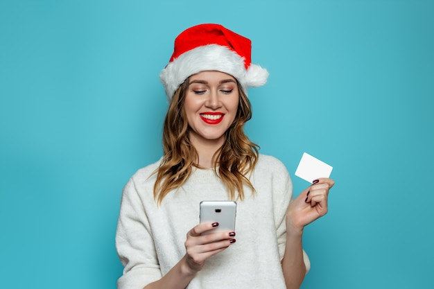 Happy young woman in santa hat smiling and holding credit card and looking into mobile phone isolated on blue  wall