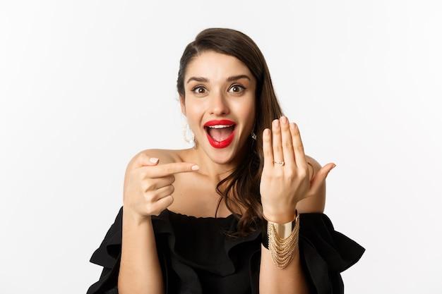 Счастливая молодая женщина, говоря «да», стать невестой, указывая на обручальное кольцо на пальце и довольная улыбка, стоя на белом фоне.