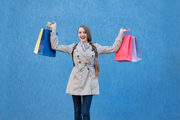 Happy young woman shopaholic with colorful bags. blue street wall on surface