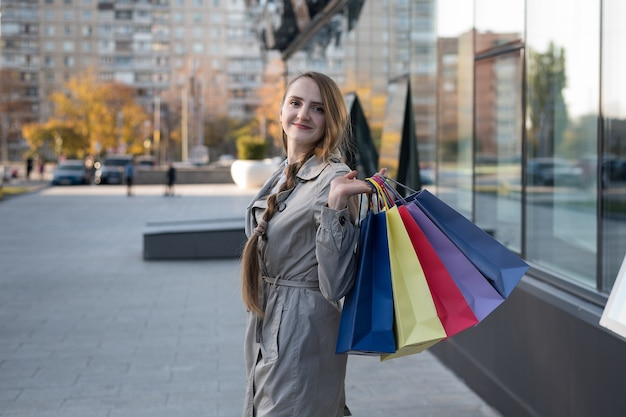 Счастливый шопоголик молодой женщины с красочными сумками возле торгового центра. идут по улице.