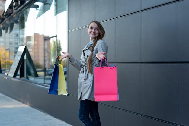 Счастливая молодая женщина шопоголика с красочными сумками возле торгового центра.