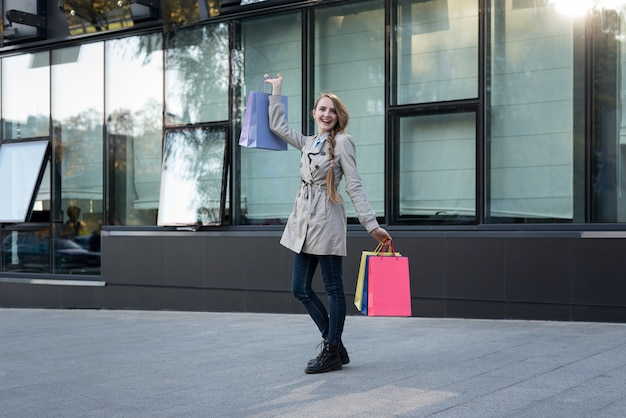 Happy young woman shopaholic with colorful bags near mall.