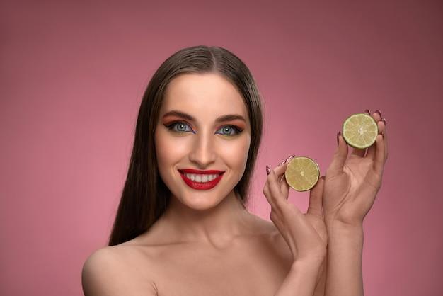 Счастливая молодая женщина показывает пользу лайма для здоровья, держа в руках две нарезанные части, выглядя очаровательно