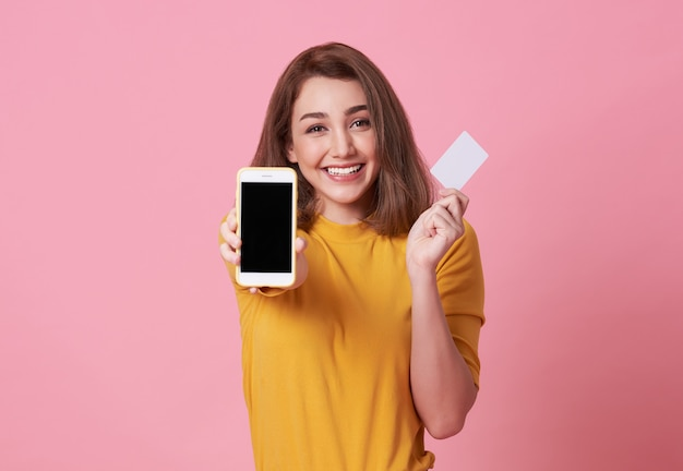 Happy young woman showing at blank screen mobile phone and credit card isolated over pink.