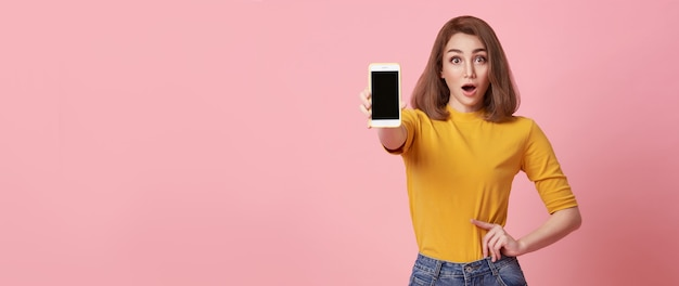 Felice giovane donna che mostra a schermo vuoto telefono cellulare e gesto di mano successo isolato su sfondo rosa.