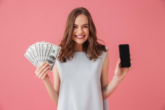 스마트 폰 및 돈의 디스플레이 보여주는 행복 한 젊은 여자.