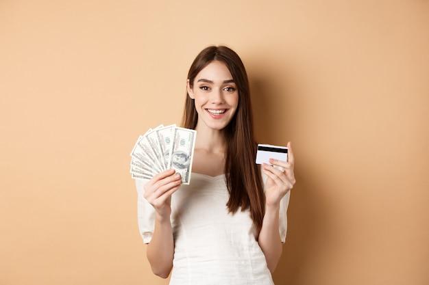 幸せな若い女性は、ベージュの背景に立って、ドル札とプラスチックのクレジットカードを表示し、満足して笑って、お金を稼ぎ、買い物をしています。