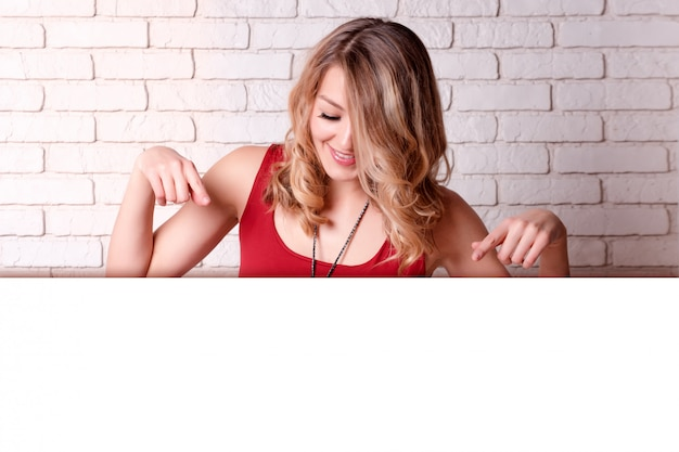 Happy young woman showing down copyspace pointing. blond young female pointing fingers away.